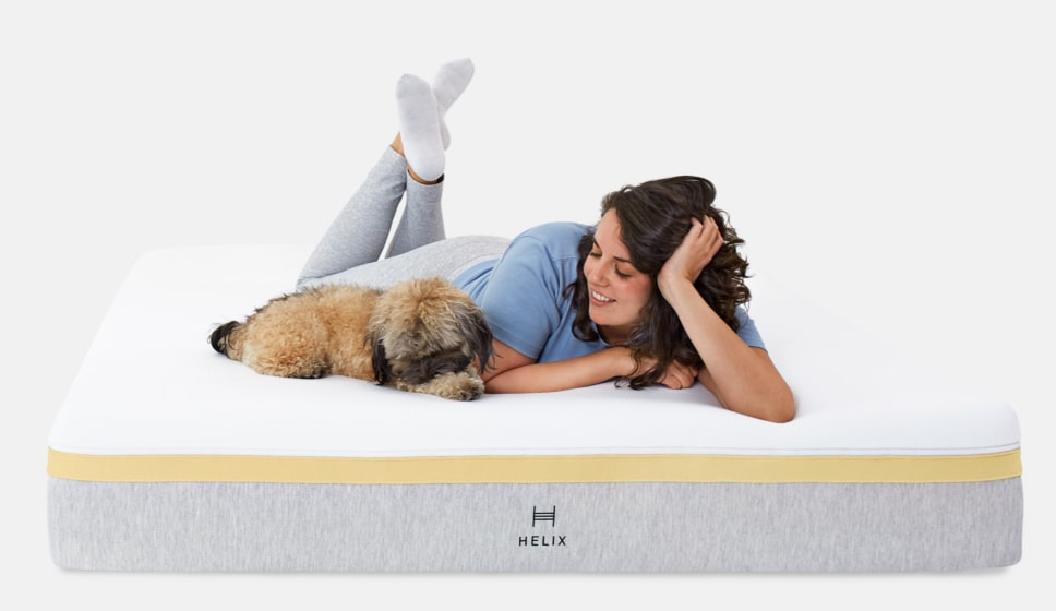 woman laying on helix bed with dog