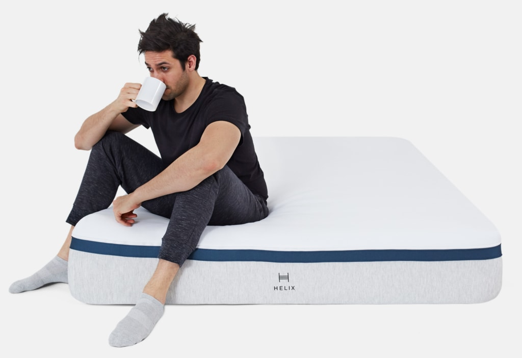 man drinking out of cup while sitting on a helix mattress