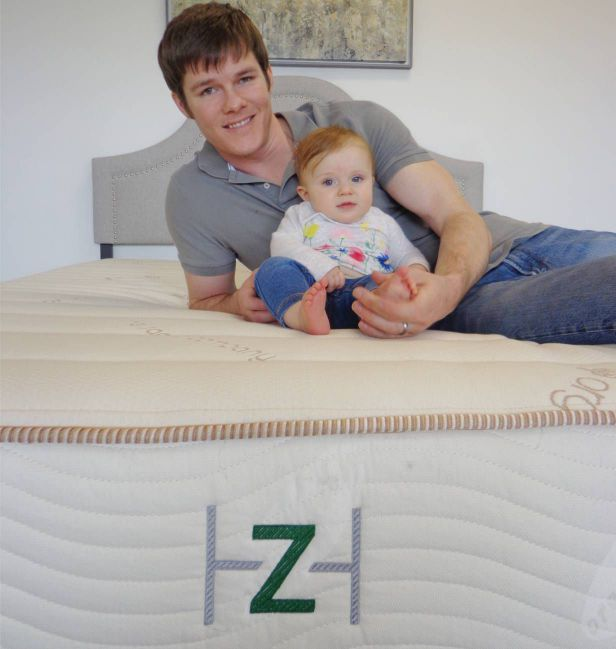 man and baby on a mattress
