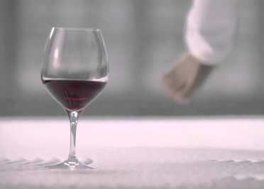 glass of wine sitting on a bed