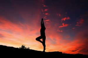 person doing yoga in front of sunset