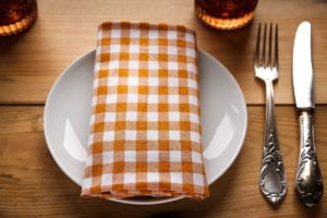 white plate with orange checkered napkin on top and silverware to the right