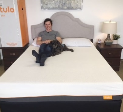 person and dog on a bed
