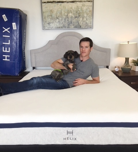 man laying with dog on helix mattress