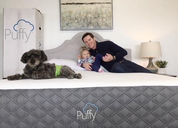 dog and people sitting on mattress