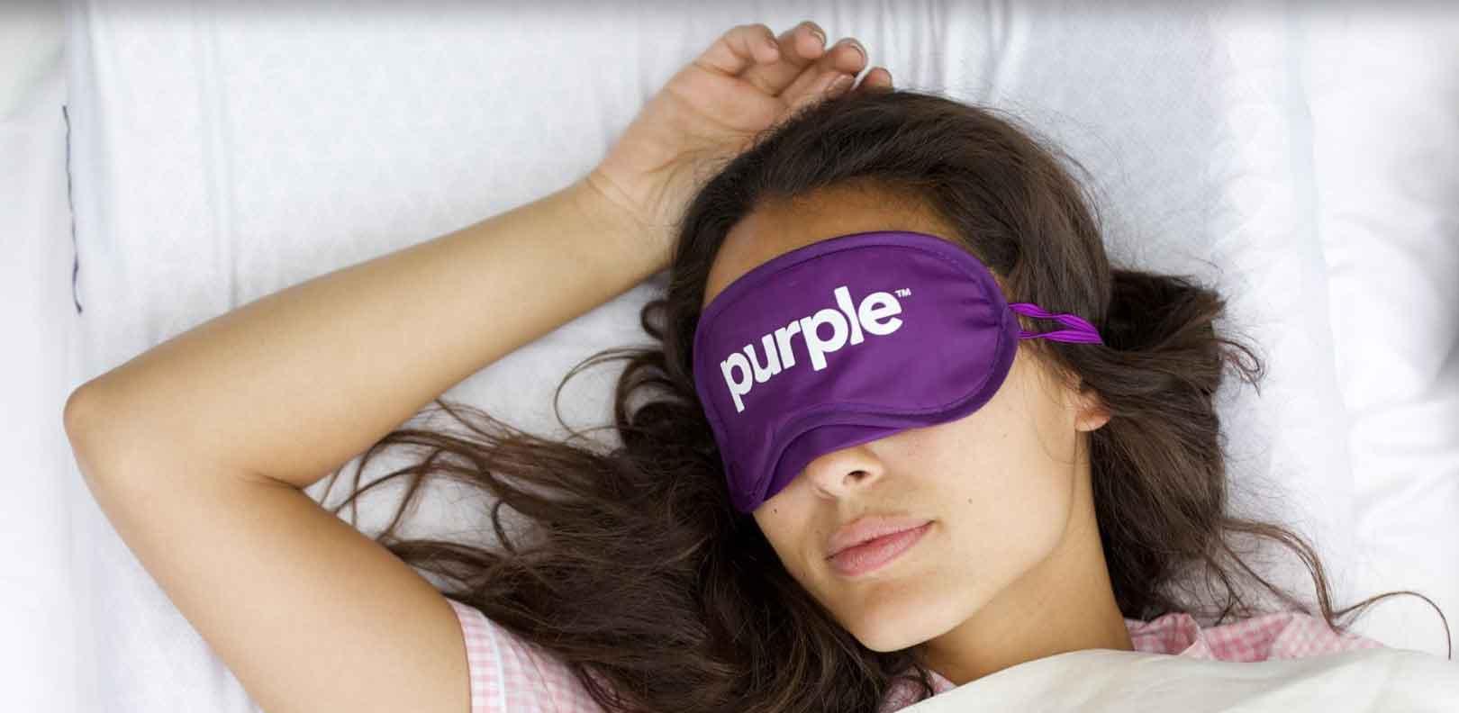 woman sleeping with purple sleep mask
