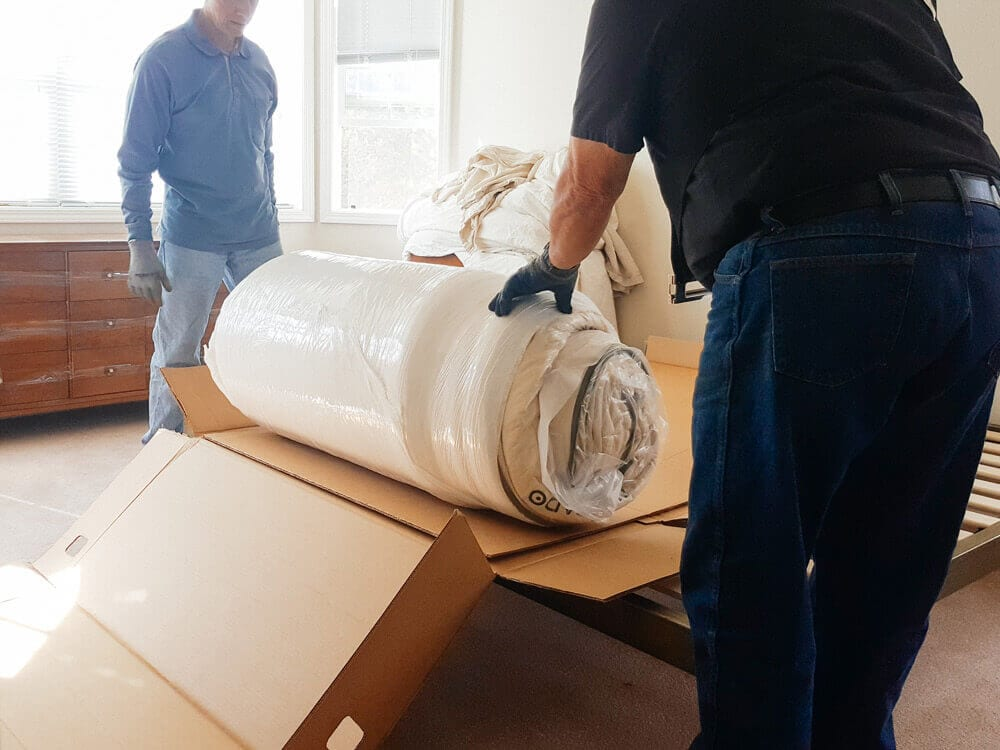 2 movers unboxing a mattress