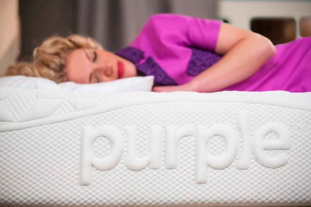 woman laying on purple mattress pink