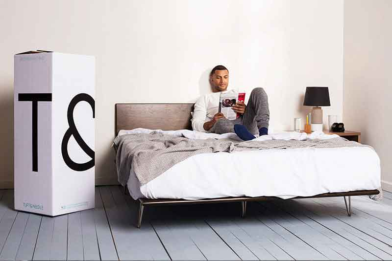 man laying down reading on bed