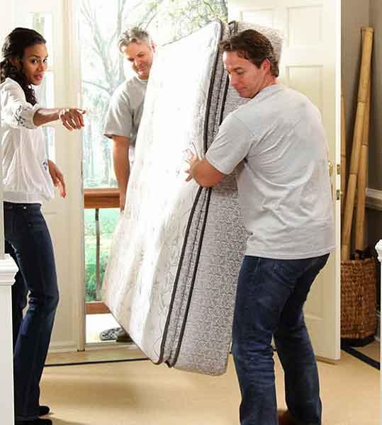 two men carrying bed woman directing