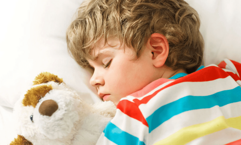 best mattress for kids - boy sleeping with stuffed animal