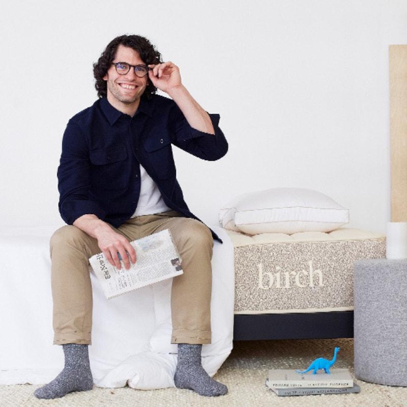 man sitting on birch mattress edge support