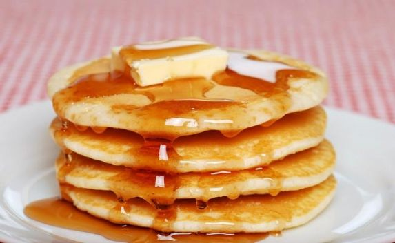 steaming hot pancakes with butter and syrup