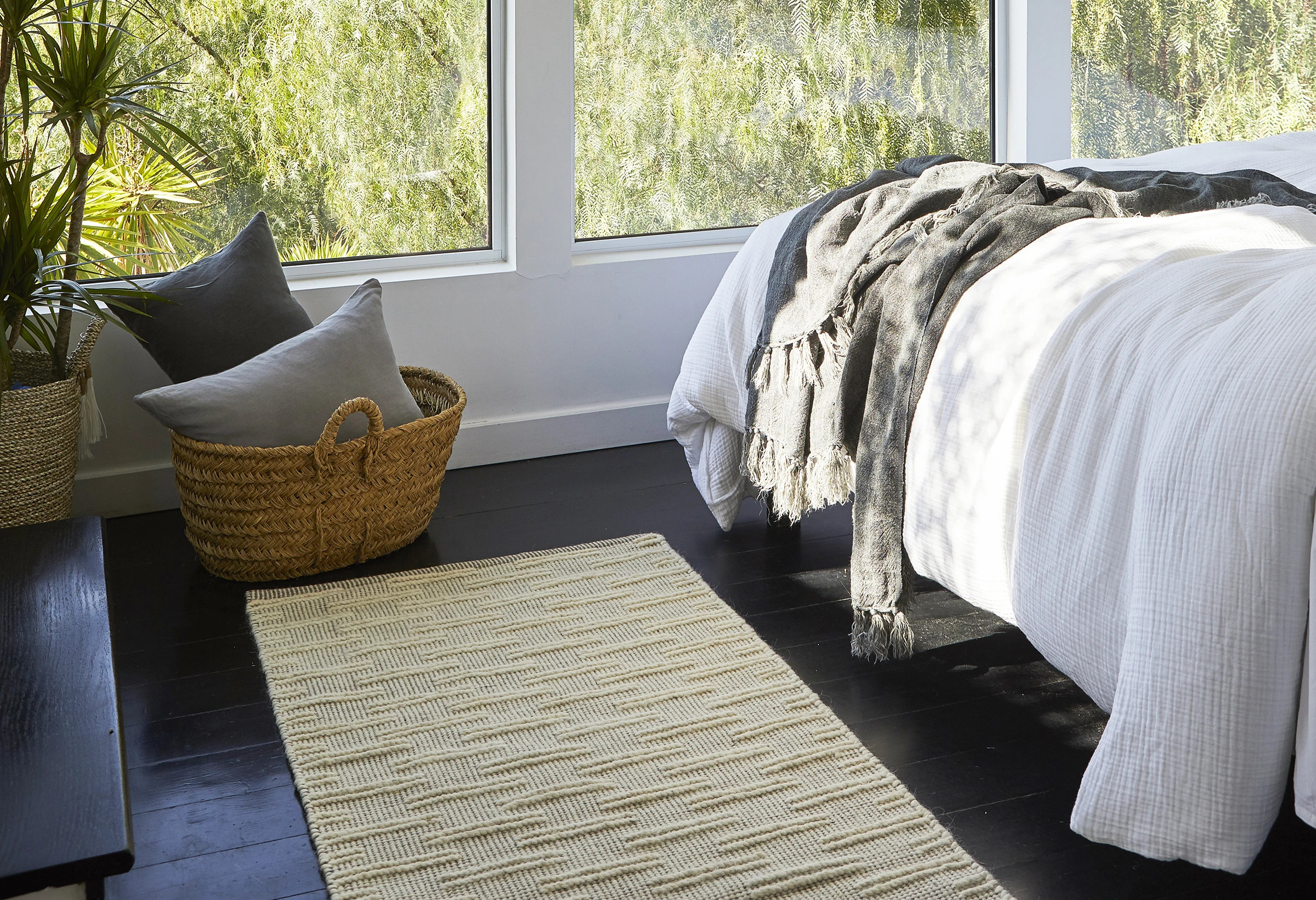 wonderful textured rug at the end of a bed